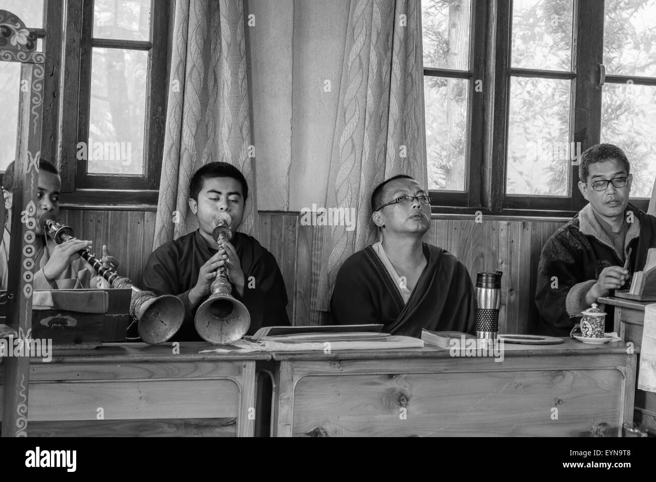 Buddhist priests, Lamas, praying inside a monastery in India, playing traditional flute, gong with copy space in - Stock Image