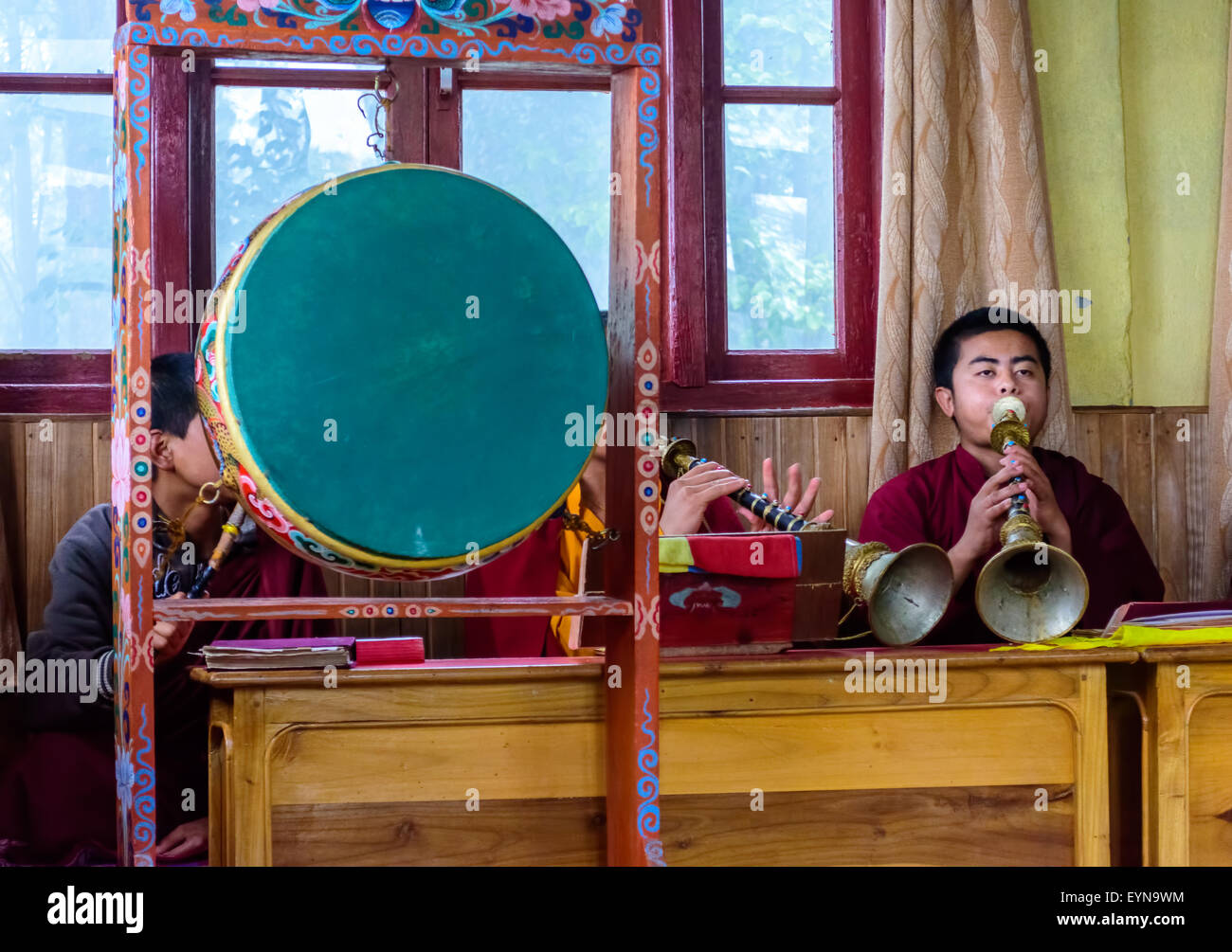 Buddhist priests, Lamas, praying inside a monastery in India, playing traditional flute, gong with copy space - Stock Image