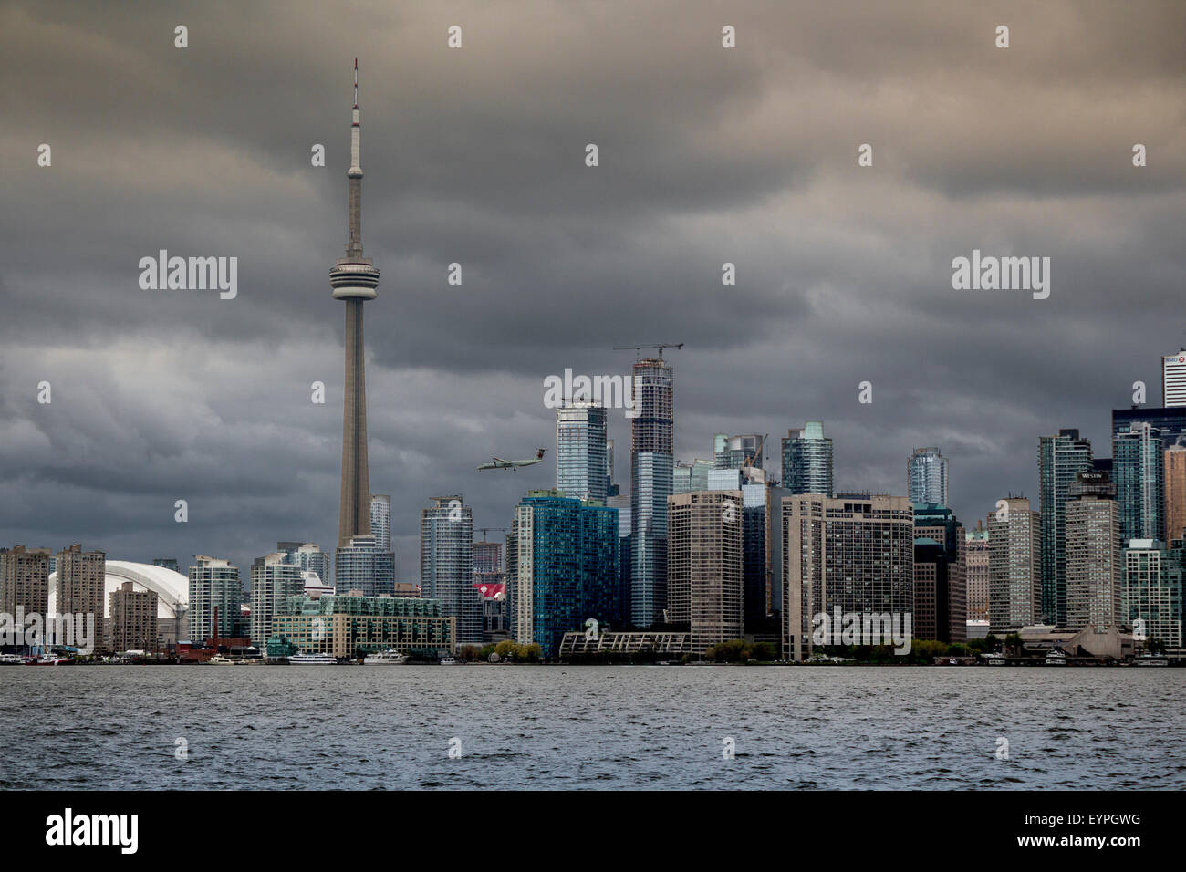 cityscape-of-the-city-of-toronto-over-a-stormy-day-with-plane-flying-EYPGWG.jpg