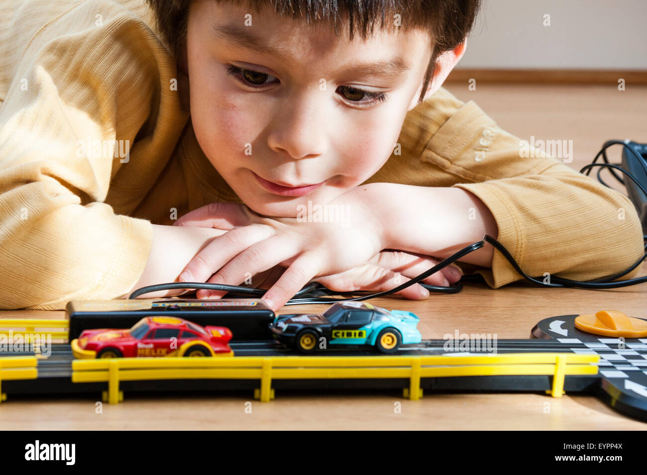 6 to 9 year old Caucasian child, boy. Indoor. Laying on floor watching scalextric racing car set Stock Photo
