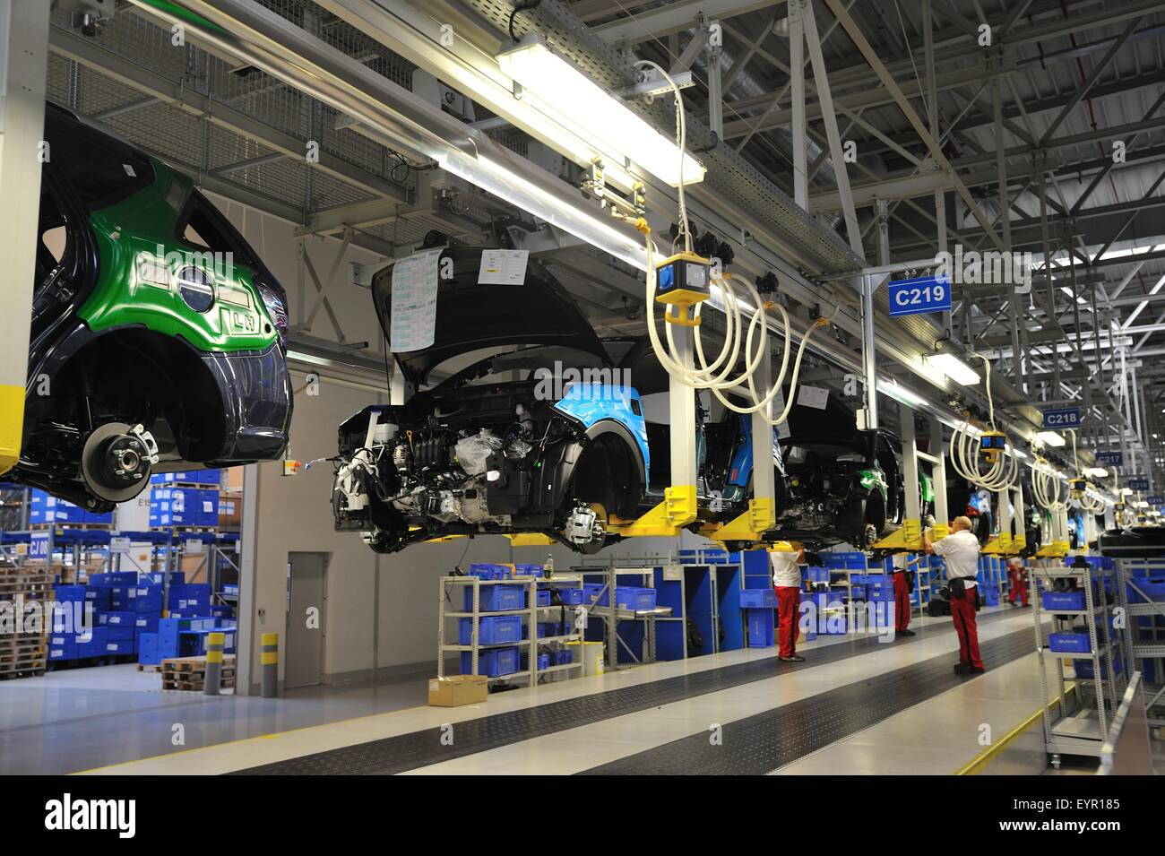 Inside a modern car factory, vehicles and parts move through the ...