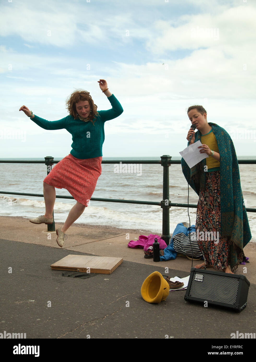Sidmouth, Devon, 3rd Aug 15 A girl dances on a wooden board as another sings on the Esplanade during Sidmouth Folk Stock Photo