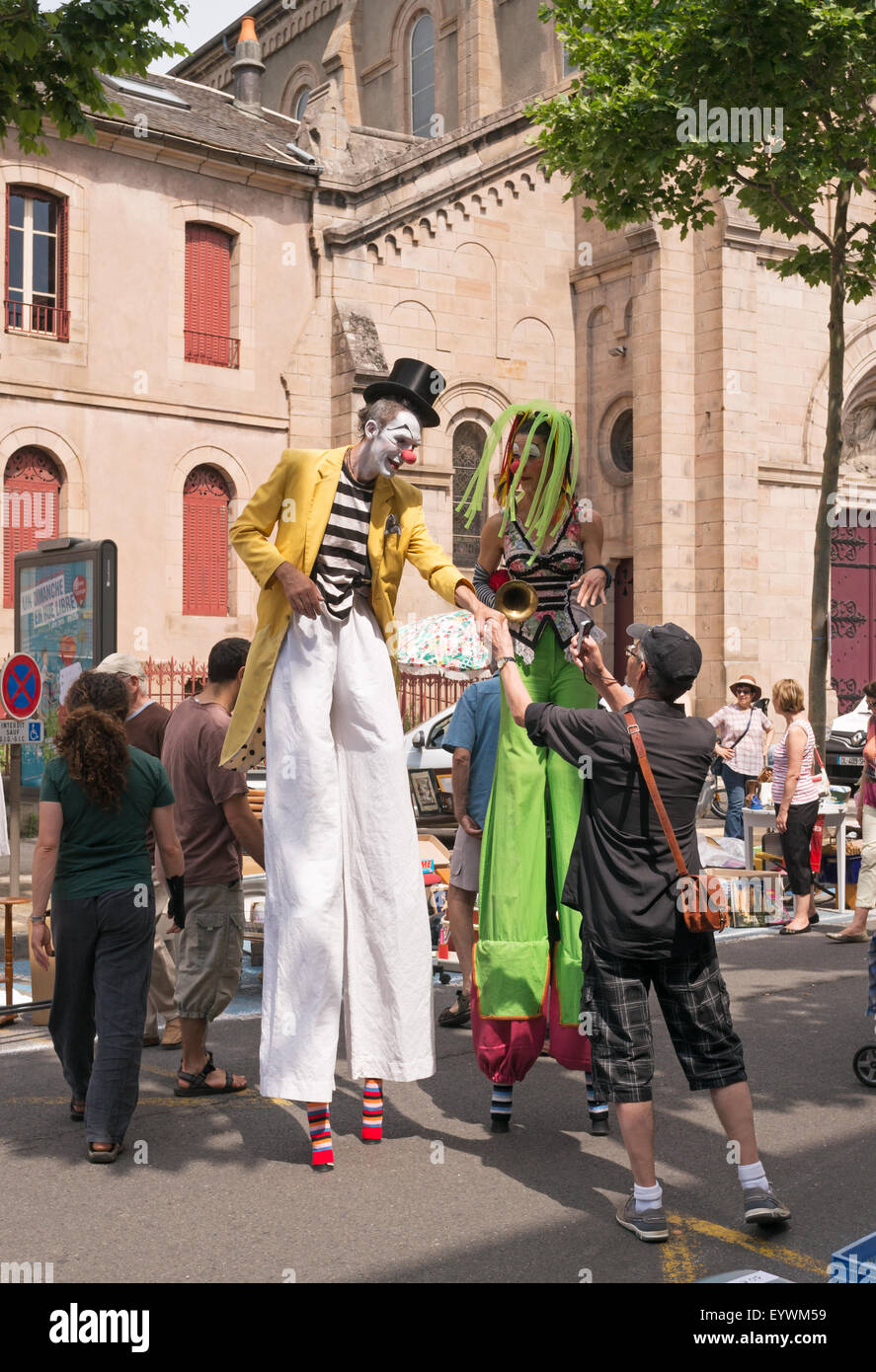 man-taking-photograph-of-stilt-walkers-a