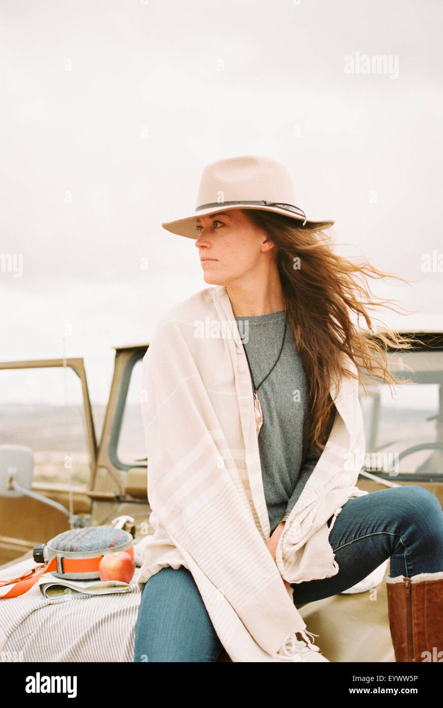 Woman wearing a hat sitting on the front of a jeep looking around her. - Stock Image