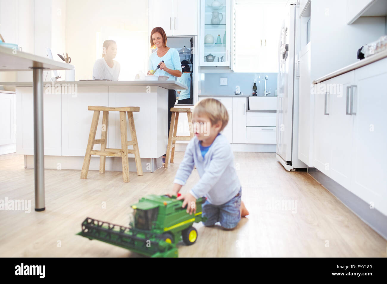 Women cooking in kitchen while boy plays with toy tractor on floor - Stock Image