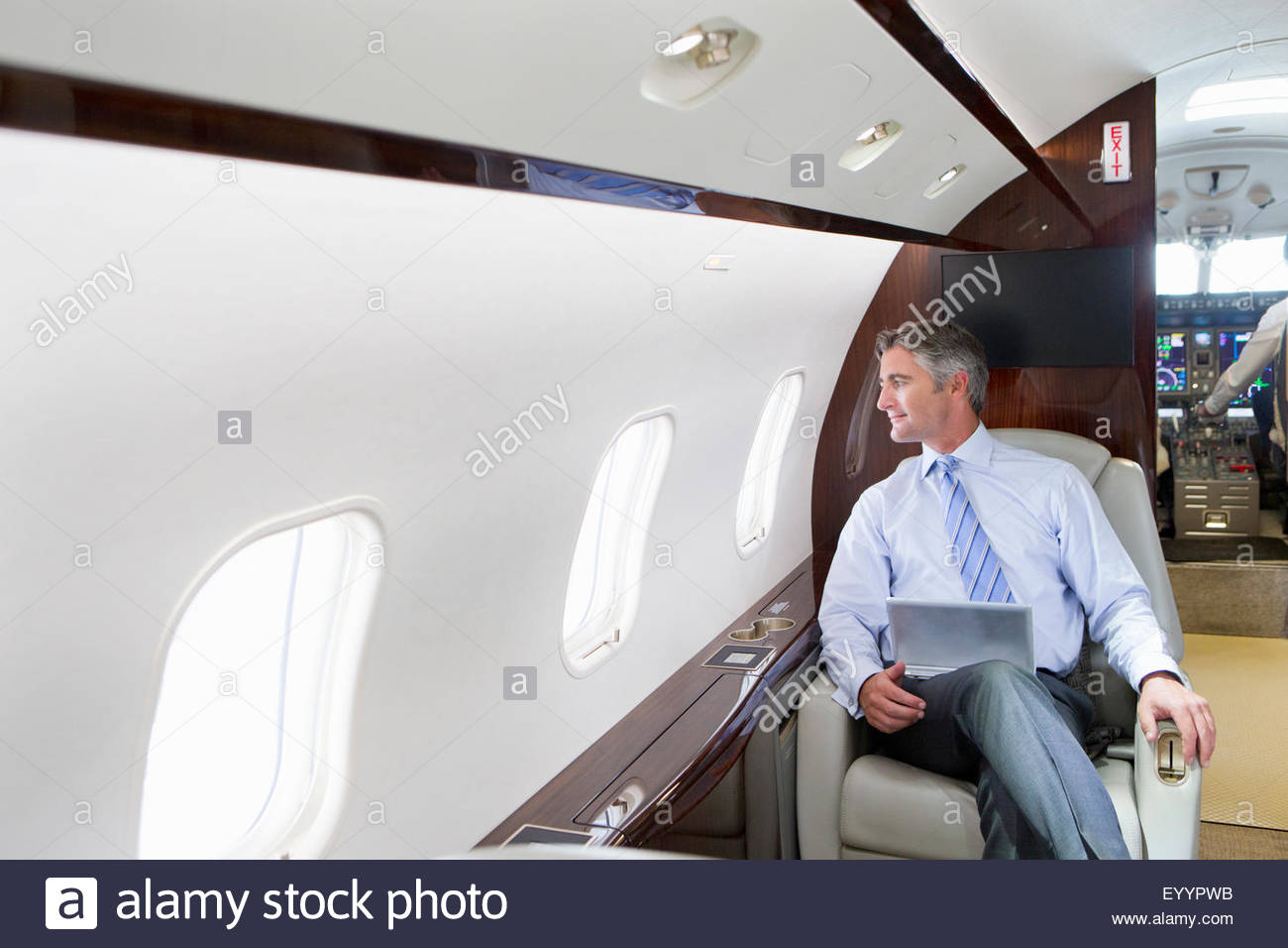 Businessman with digital tablet looking out of window on private jet - Stock Image