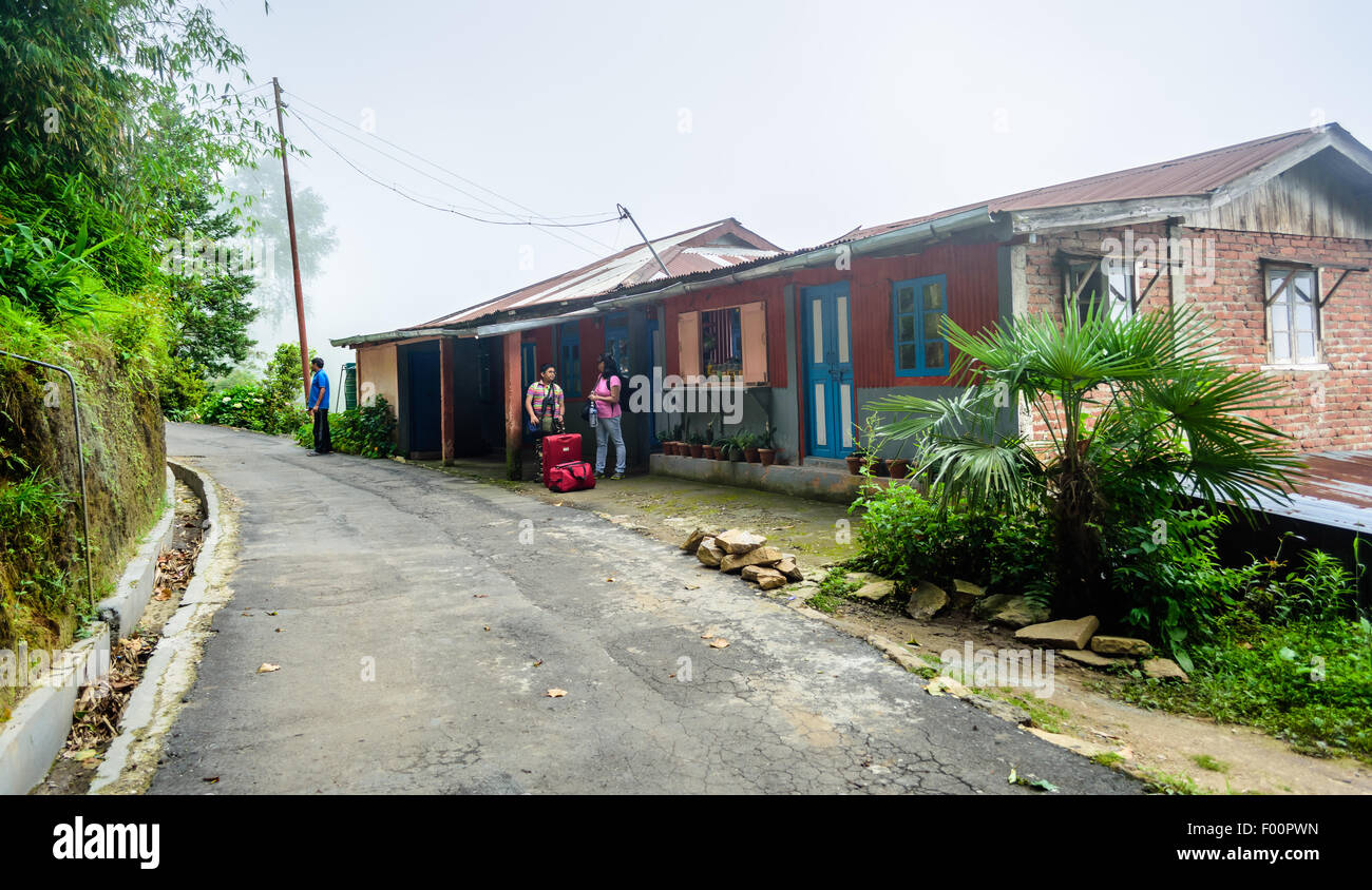 Mountain Village road with house with tourists standing in front with luggage and copy space - Stock Image