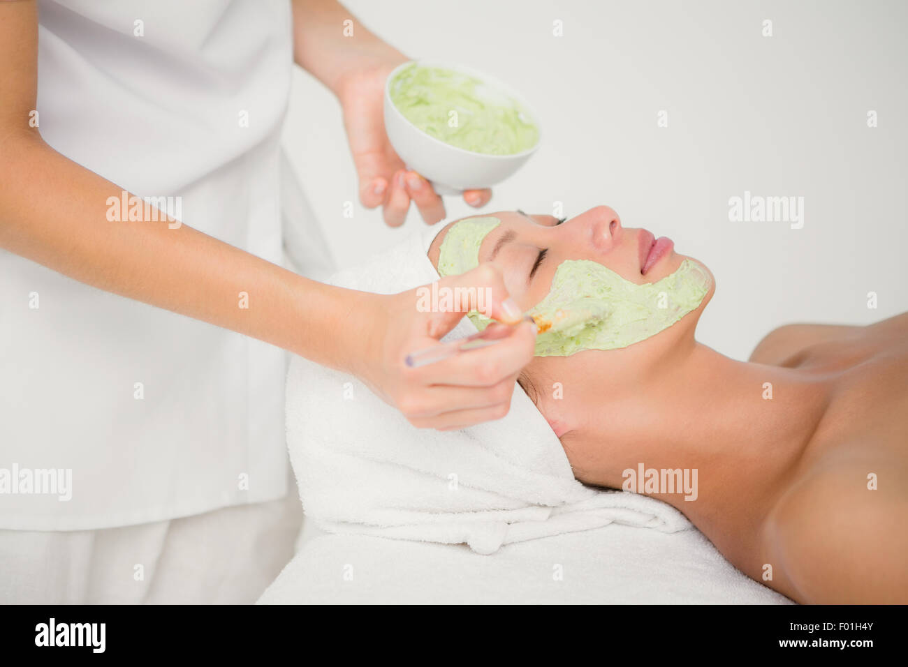 Beautiful brunette getting a facial treatment - Stock Image