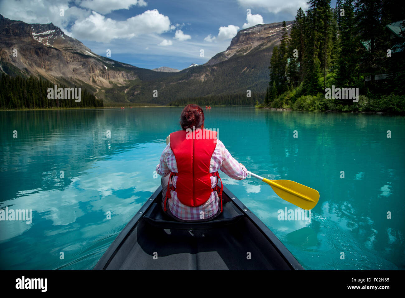 Woman canoeing in Emerald Lake, Yoho National Park, British Columbia Canada - Stock Image