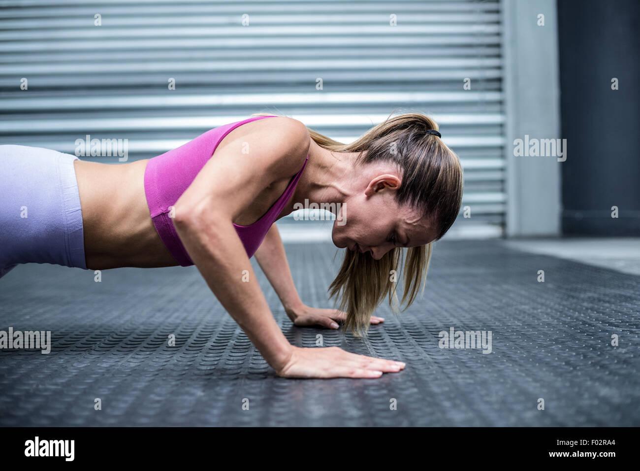 Muscular woman doing push ups - Stock Image