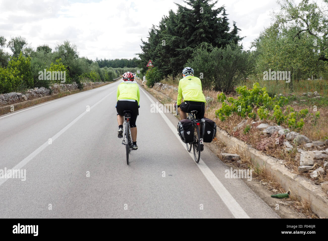 Two touring cyclists riding their bicycles on a country road Stock Photo