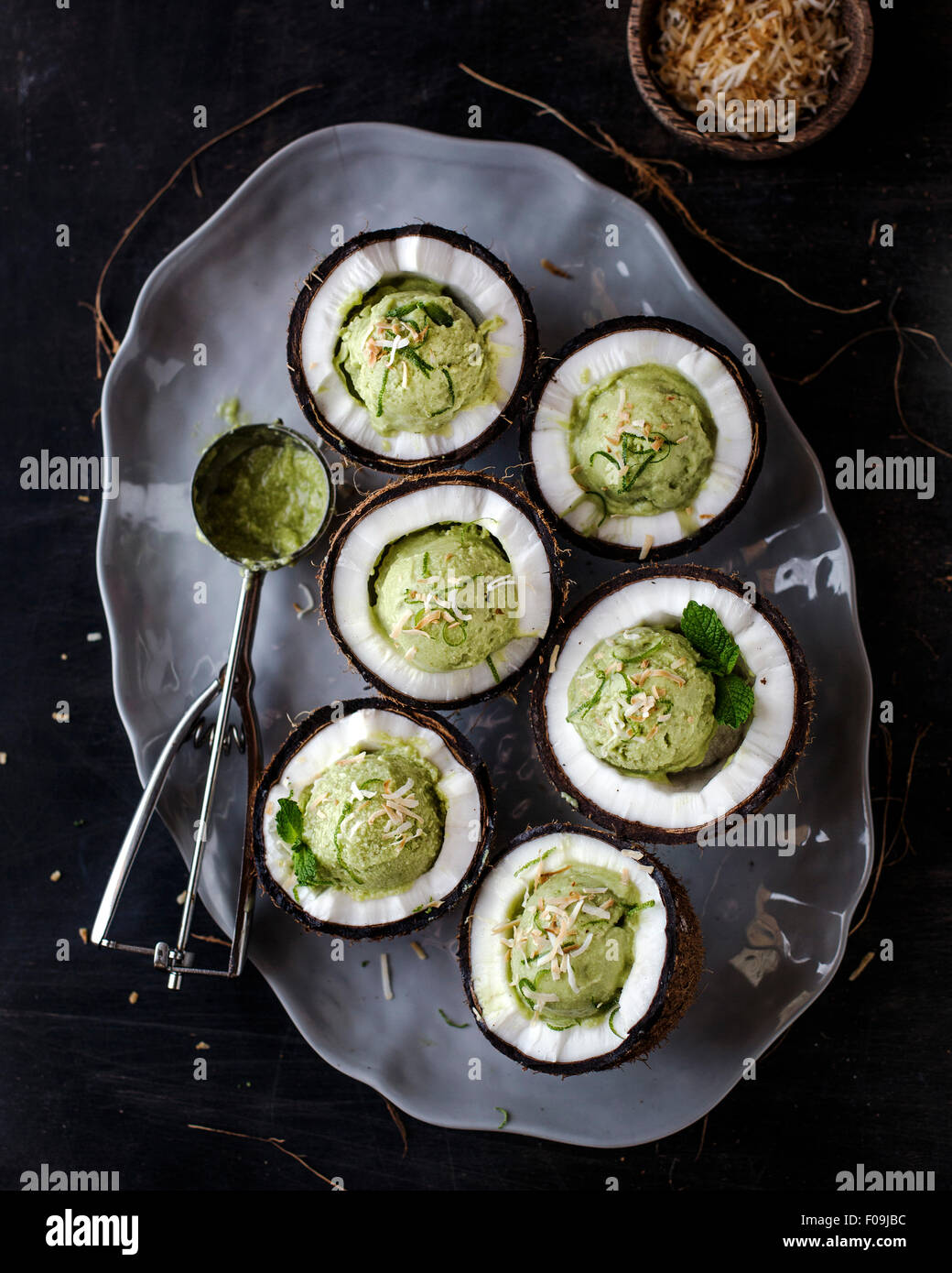 Coconut and Avocado Ice Cream served in freshly cracked coconut bowls in a dark background. - Stock Image