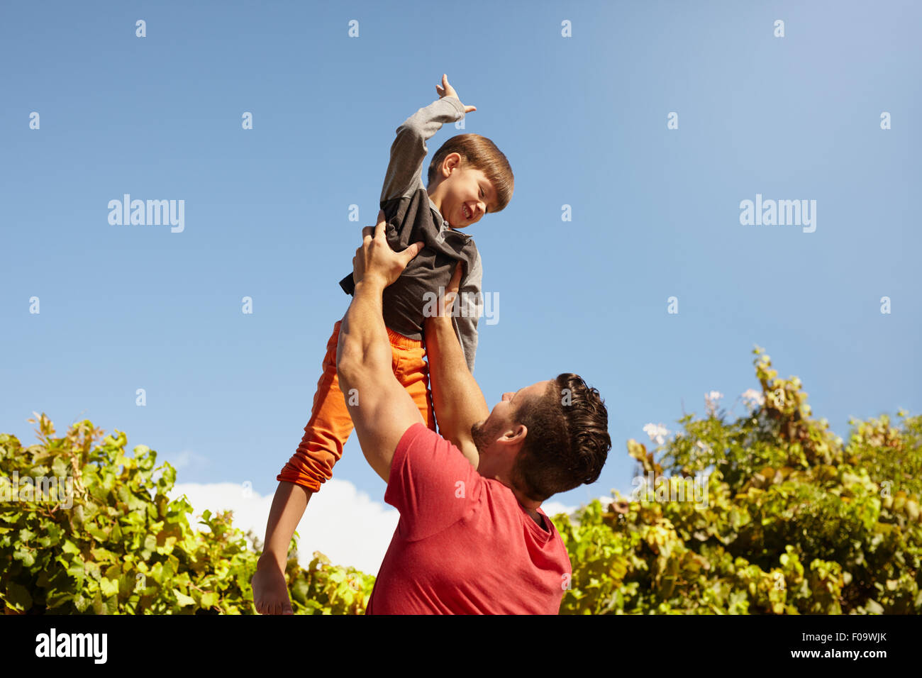 Shot of young man holding his little son high up in air against sky on a sunny day. Happy father and son having - Stock Image