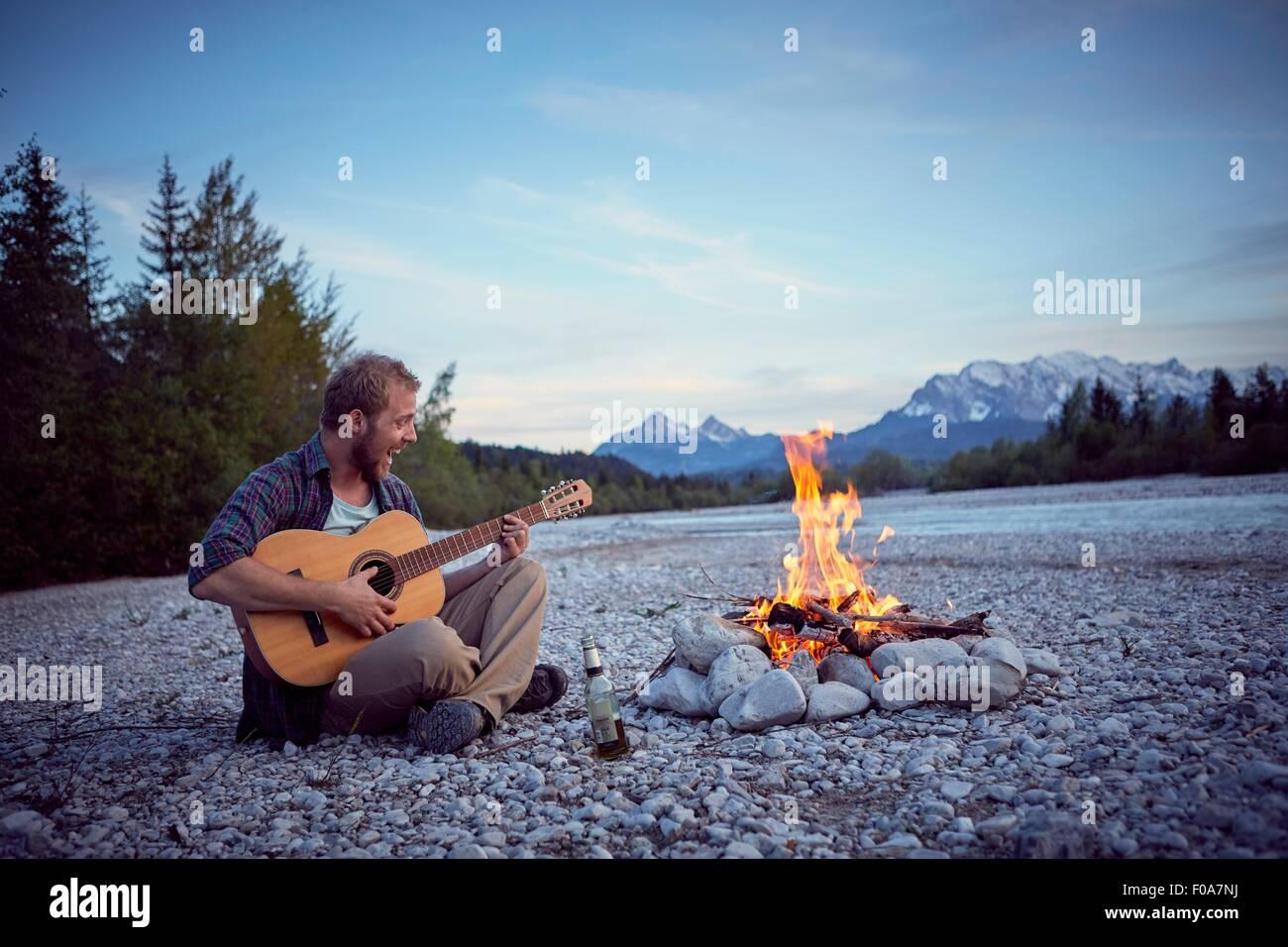 Young man sitting by campfire playing guitar, singing, Wallgau, Bavaria, Germany - Stock Image