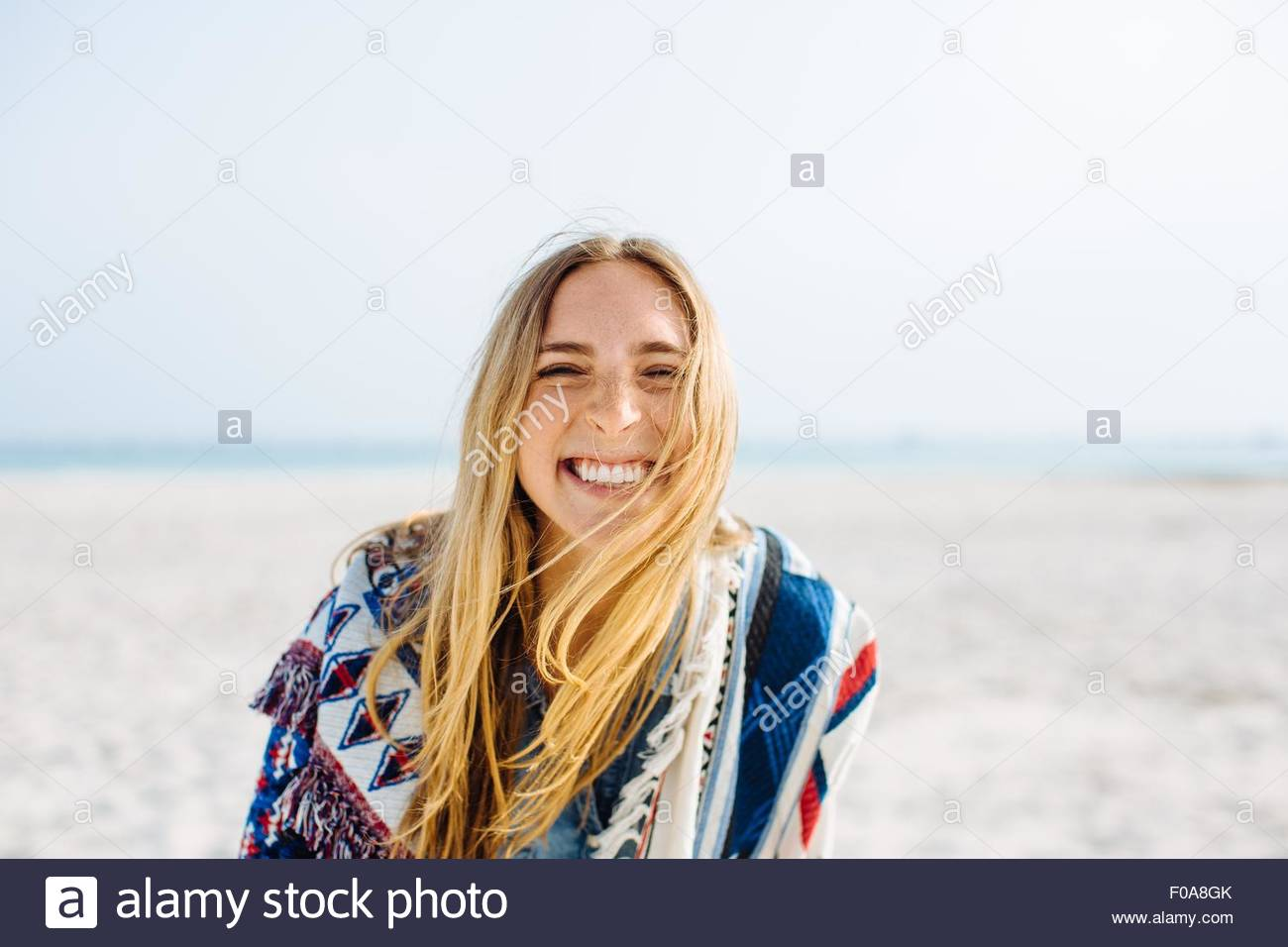 Portrait of young woman wrapped in blanket making smiley face on beach - Stock Image