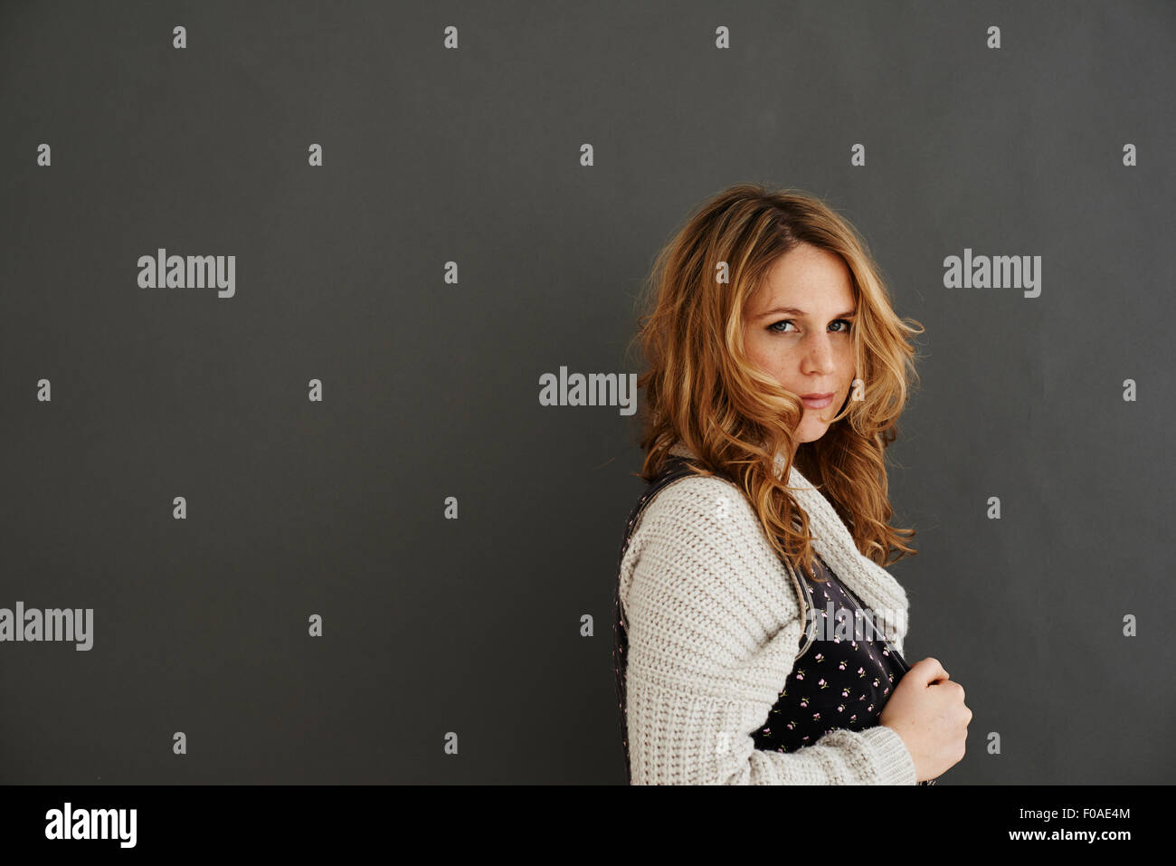 Mid adult woman side view looking at camera - Stock Image