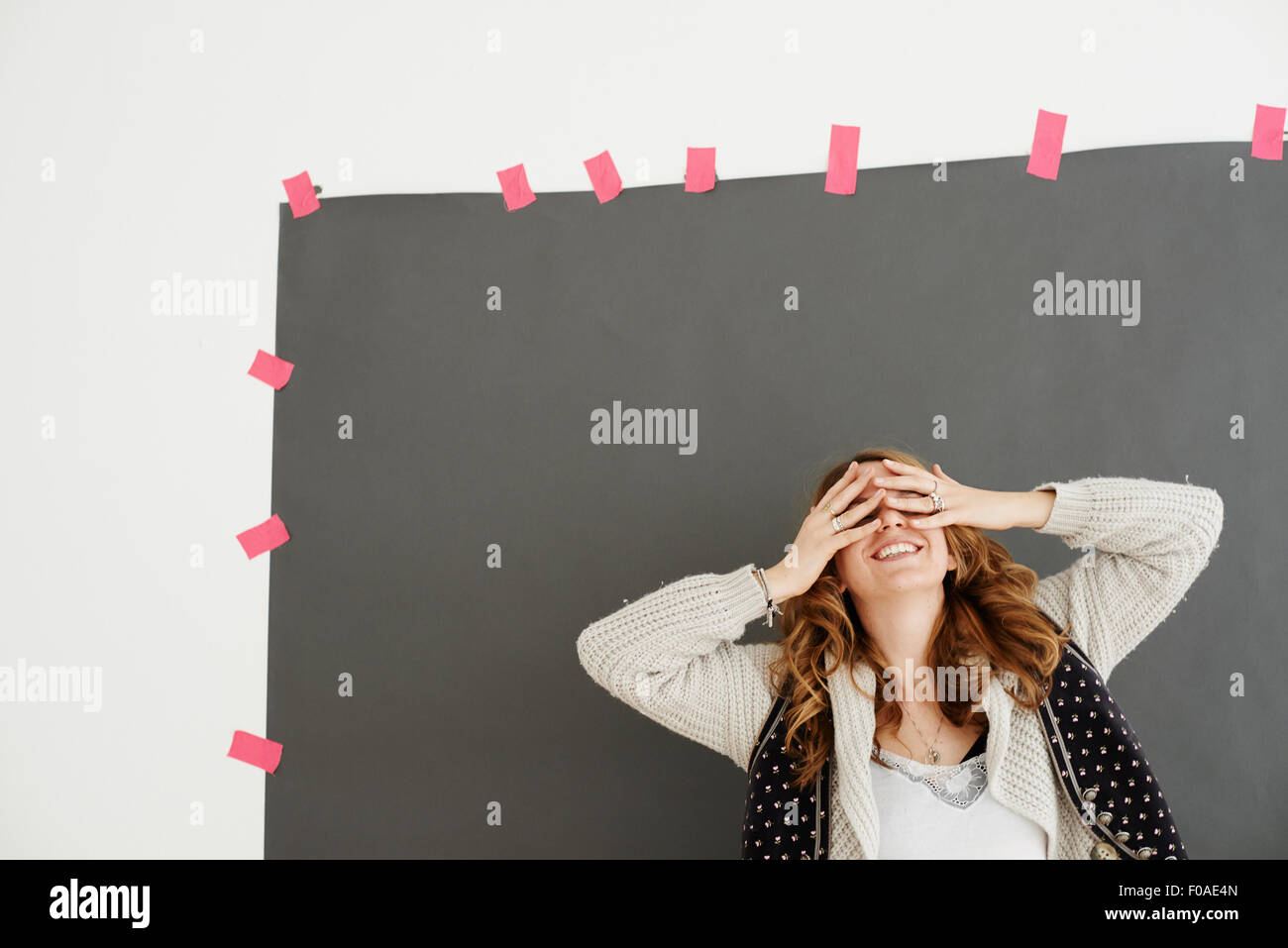 Mid adult woman smiling, hands covering eyes - Stock Image
