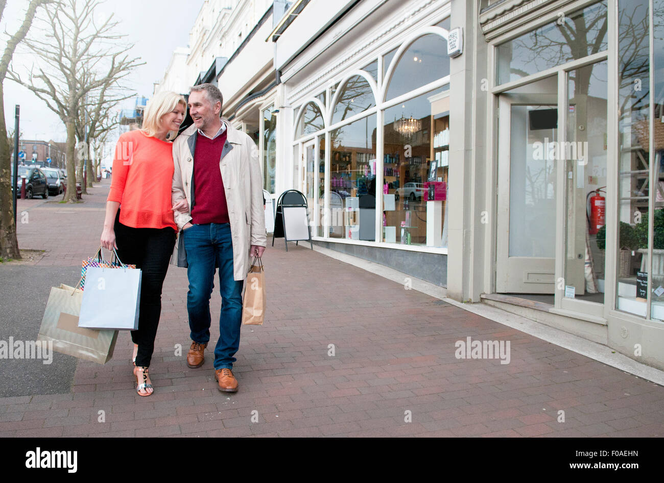 Couple carrying shopping  on village street - Stock Image