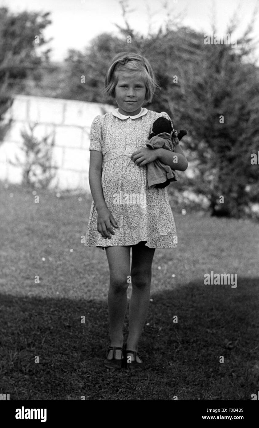 A Girl Holding A Doll In The Garden.