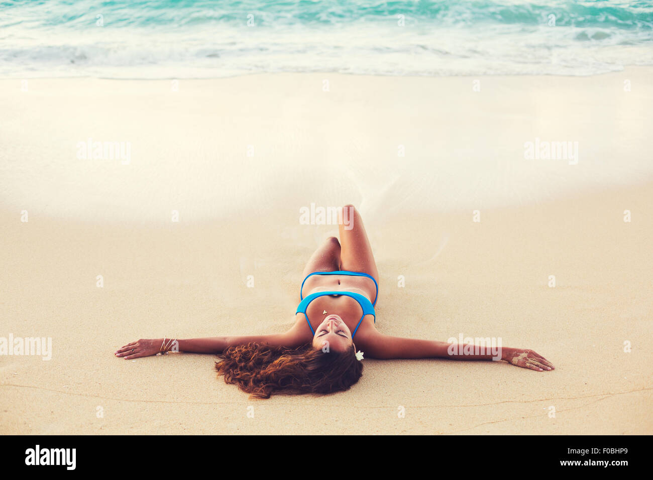 Summer Lifestyle, Beautiful Happy Carefree Young Woman Relaxing on the Beach at Sunset - Stock Image