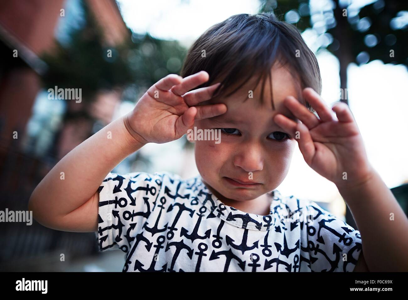 Portrait of boy crying on street - Stock Image