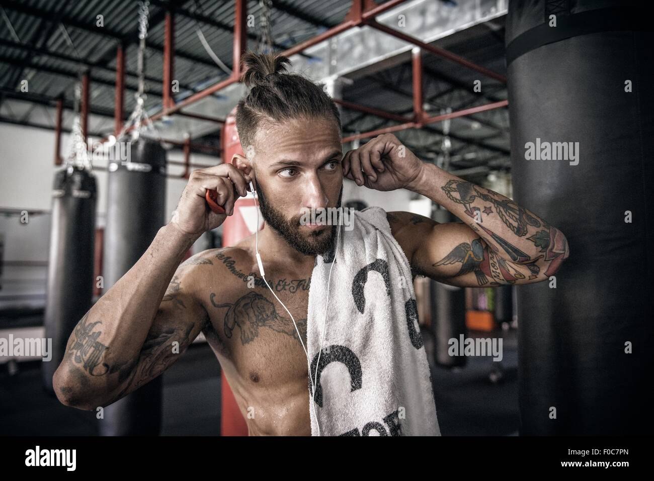 Male boxer putting in earphones at gym - Stock Image