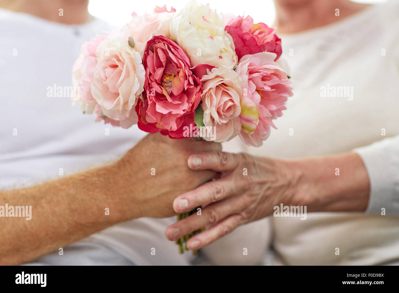 close up of senior couple with flowers - Stock Image