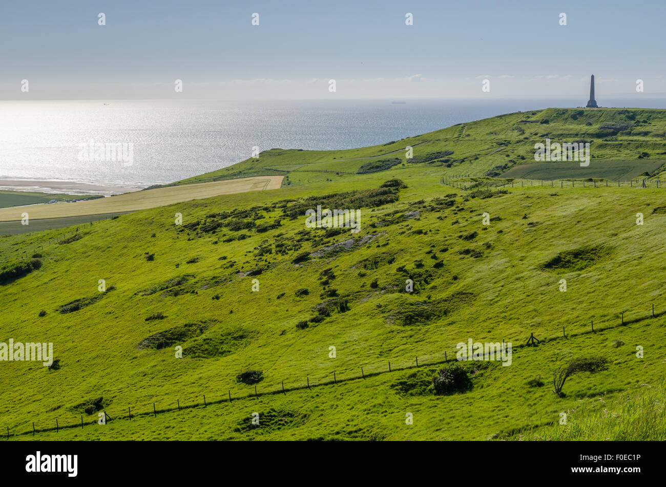 Sunset view of Cap Blanc Nez cliffs, obelisks, and Channel sea, with bomb craters in the fields. - Stock Image