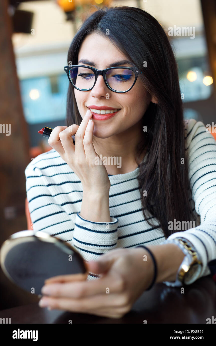 Portrait of young beautiful woman making up her face. - Stock Image