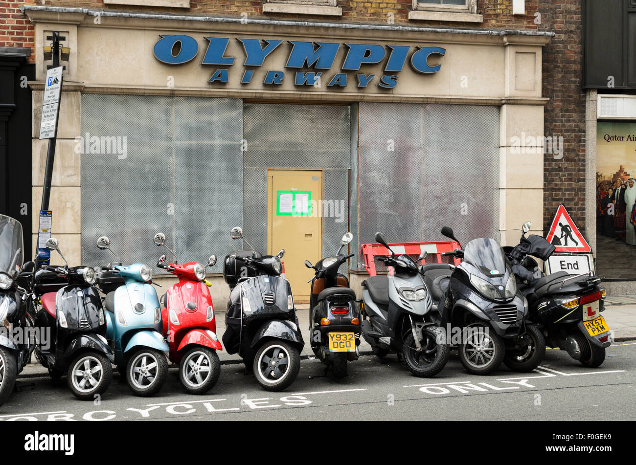 Mopeds parked outside the former Olympic Airways Office, London, England, UK. - Stock Image