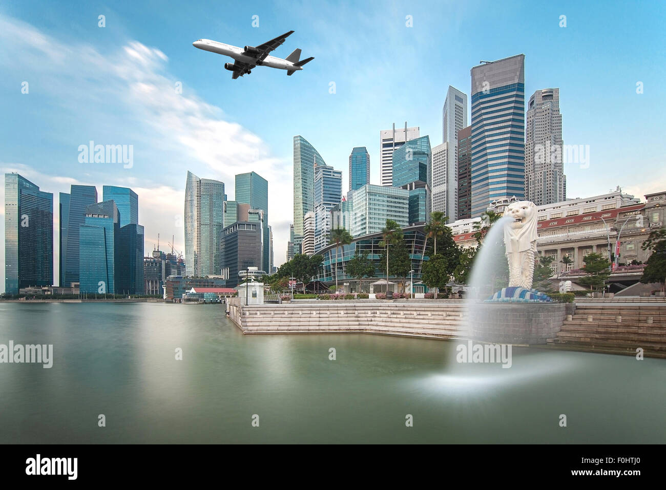 Travel, Transportation concept - Airplane flying over Singapore city in morning time - Stock Image