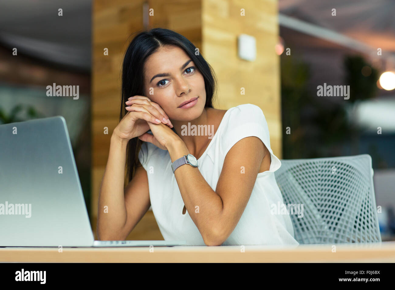 Portrait of attractive thoughtful businesswoman sitting at the desk in office and looking at camera - Stock Image