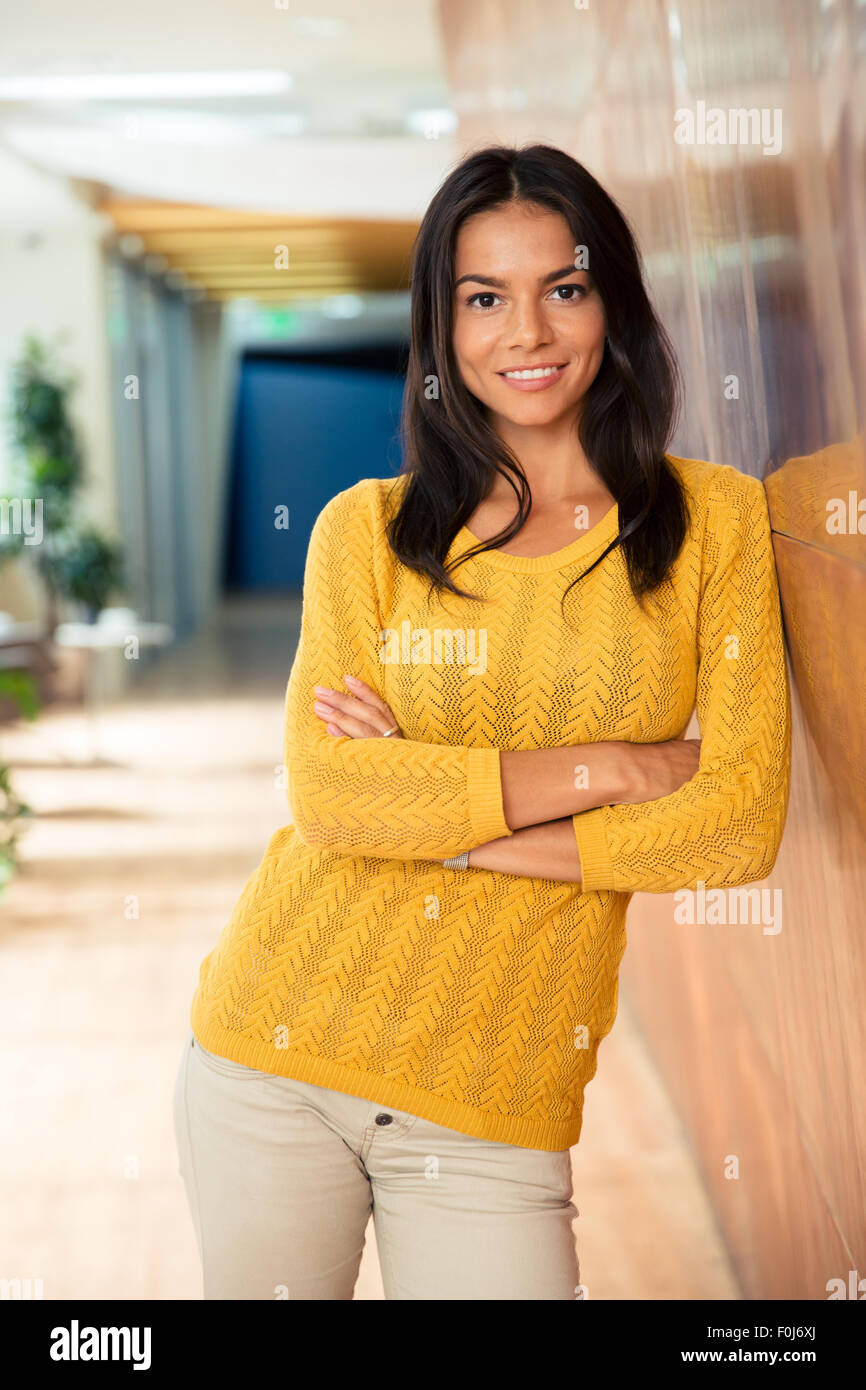 Portrait of a smiling casual businesswoman standing with arms folded in office - Stock Image