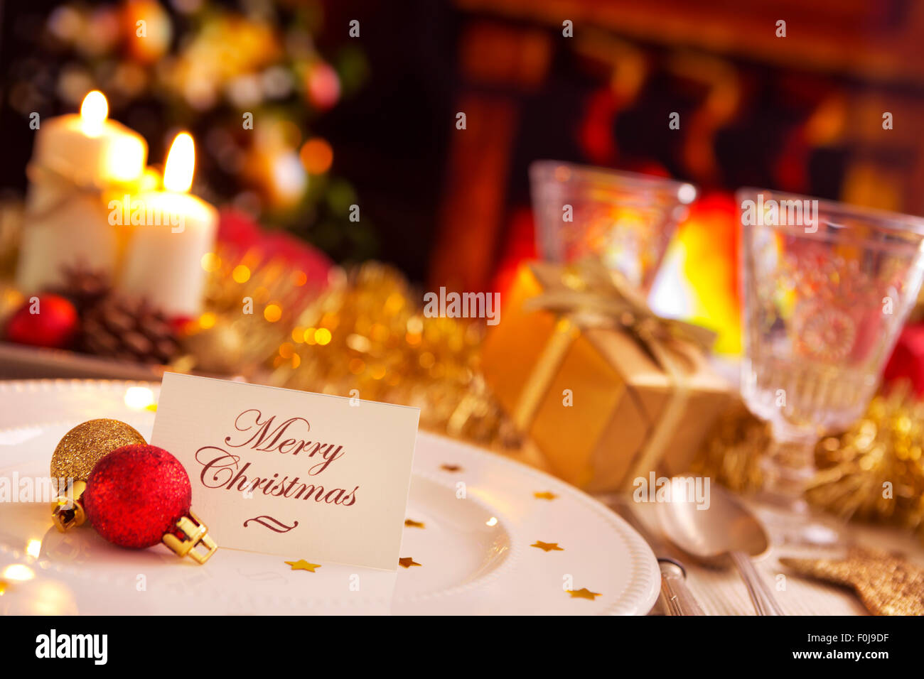 A romantic Christmas dinner table setting with candles and Christmas decorations. On the plate a note with the words \u0027Merry Chri & A romantic Christmas dinner table setting with candles and Christmas ...