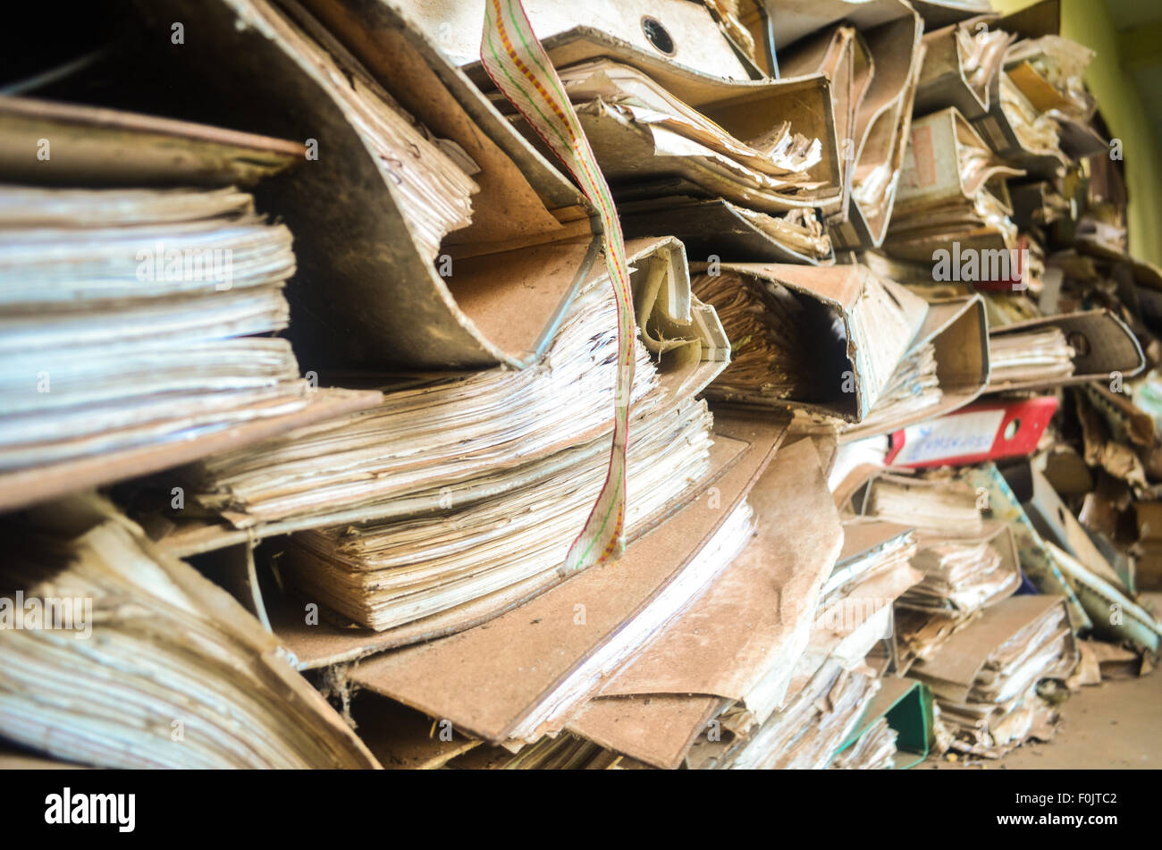 Old yellowish files piled up and covered with dust - Stock Image