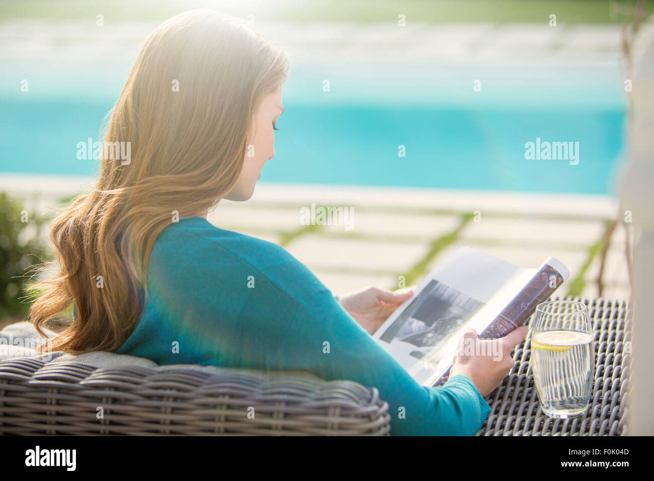 Brunette woman reading magazine at luxury poolside - Stock Image