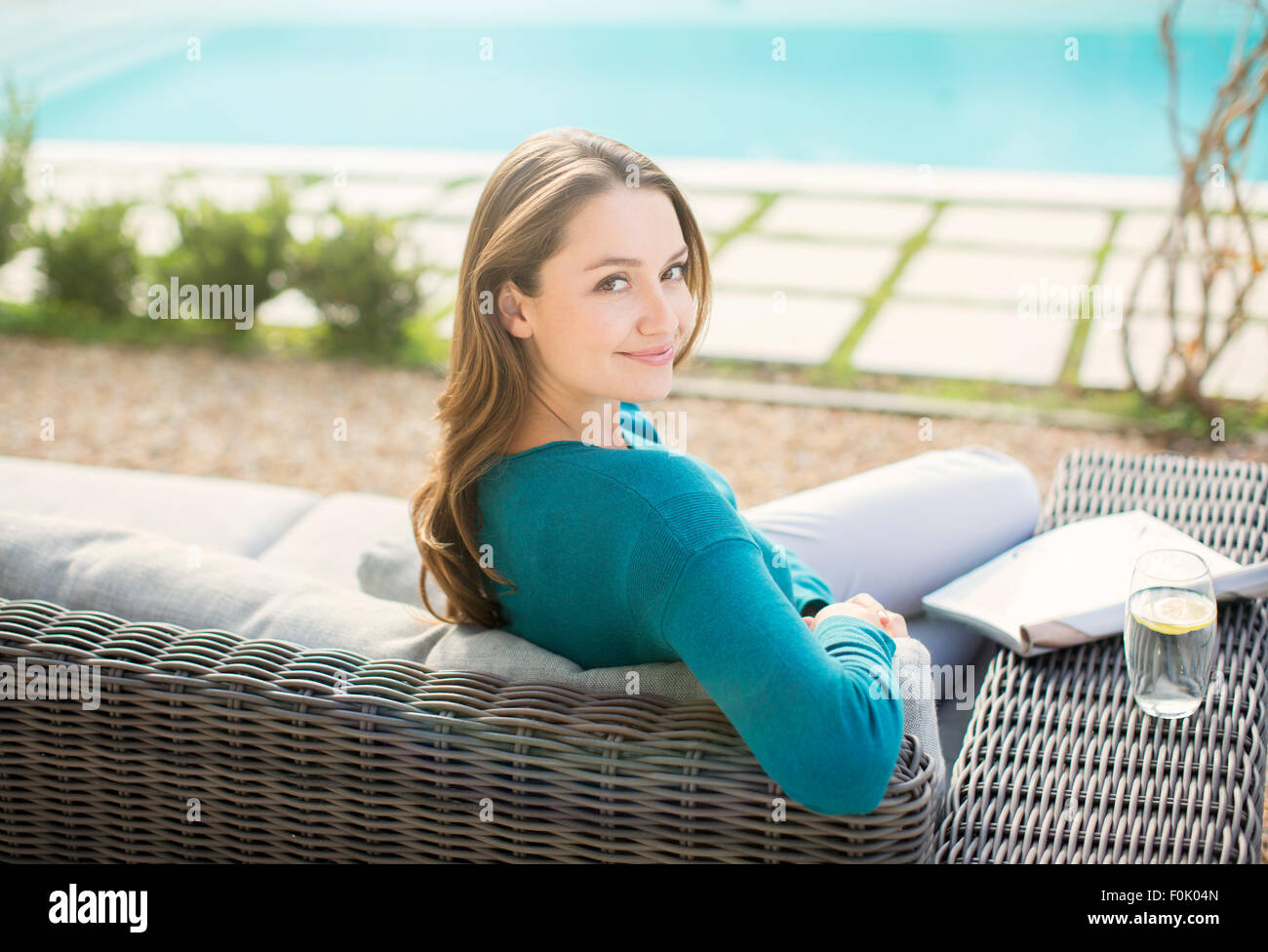 Portrait smiling woman reading magazine at luxury poolside - Stock Image