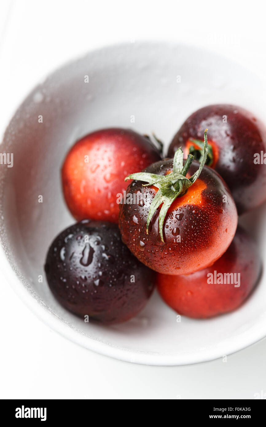 Black tomatoes in a white bowl - Stock Image