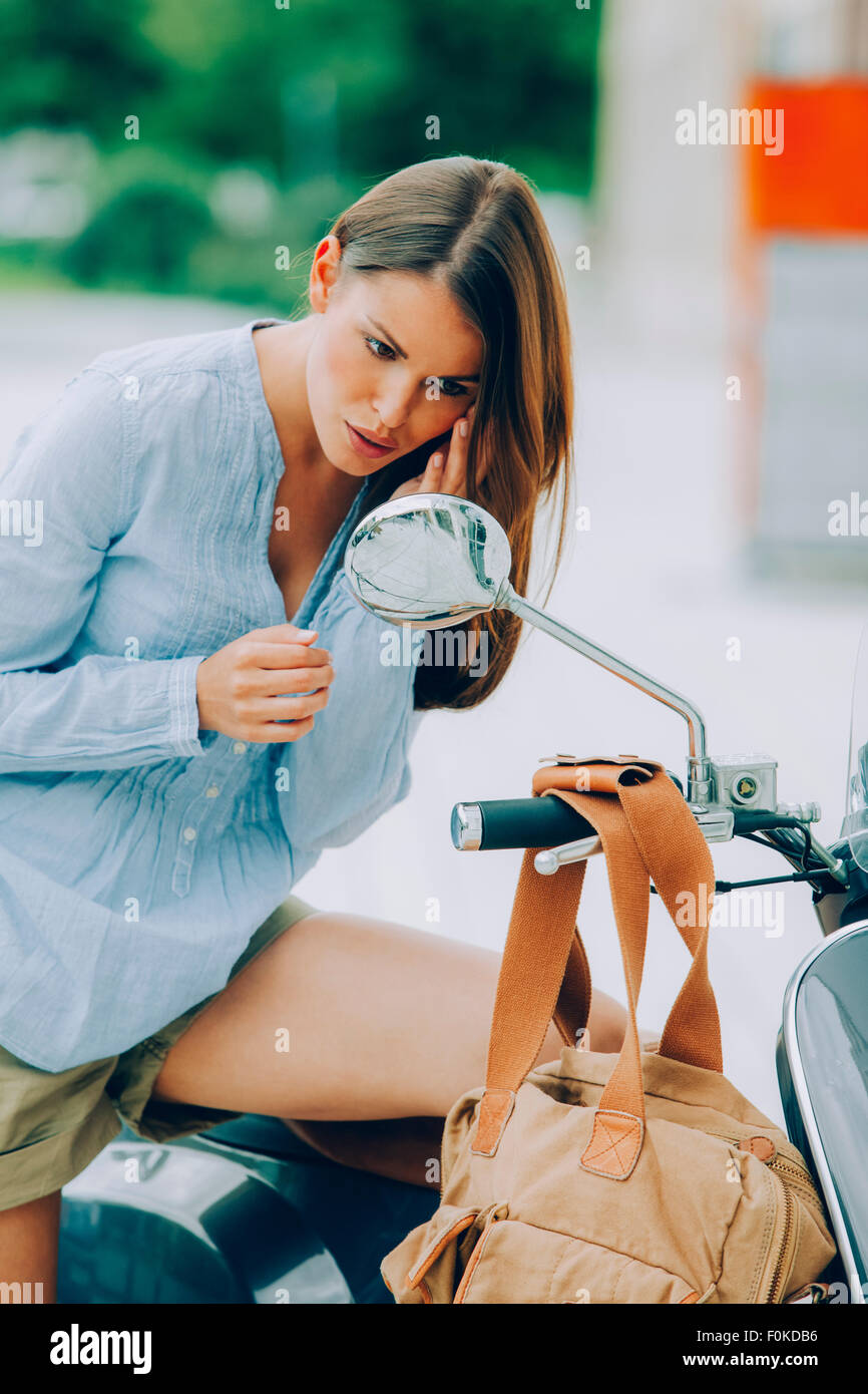 Young woman on motor scooter looking in rear-view mirror - Stock Image