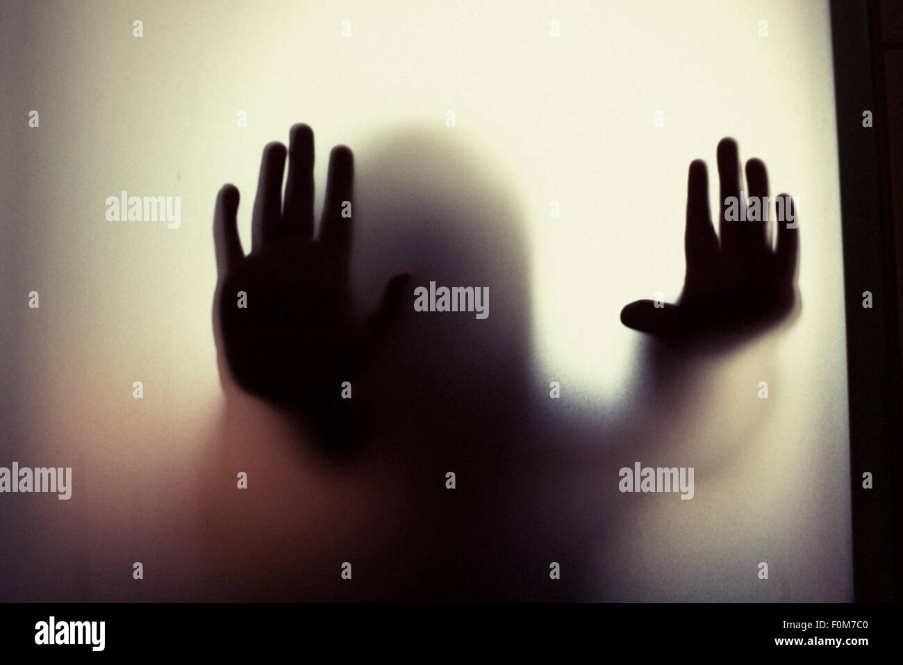 Silhouette of little child holding out hands. Conceptual image of childhood fears, abuse and safety of children. - Stock Image