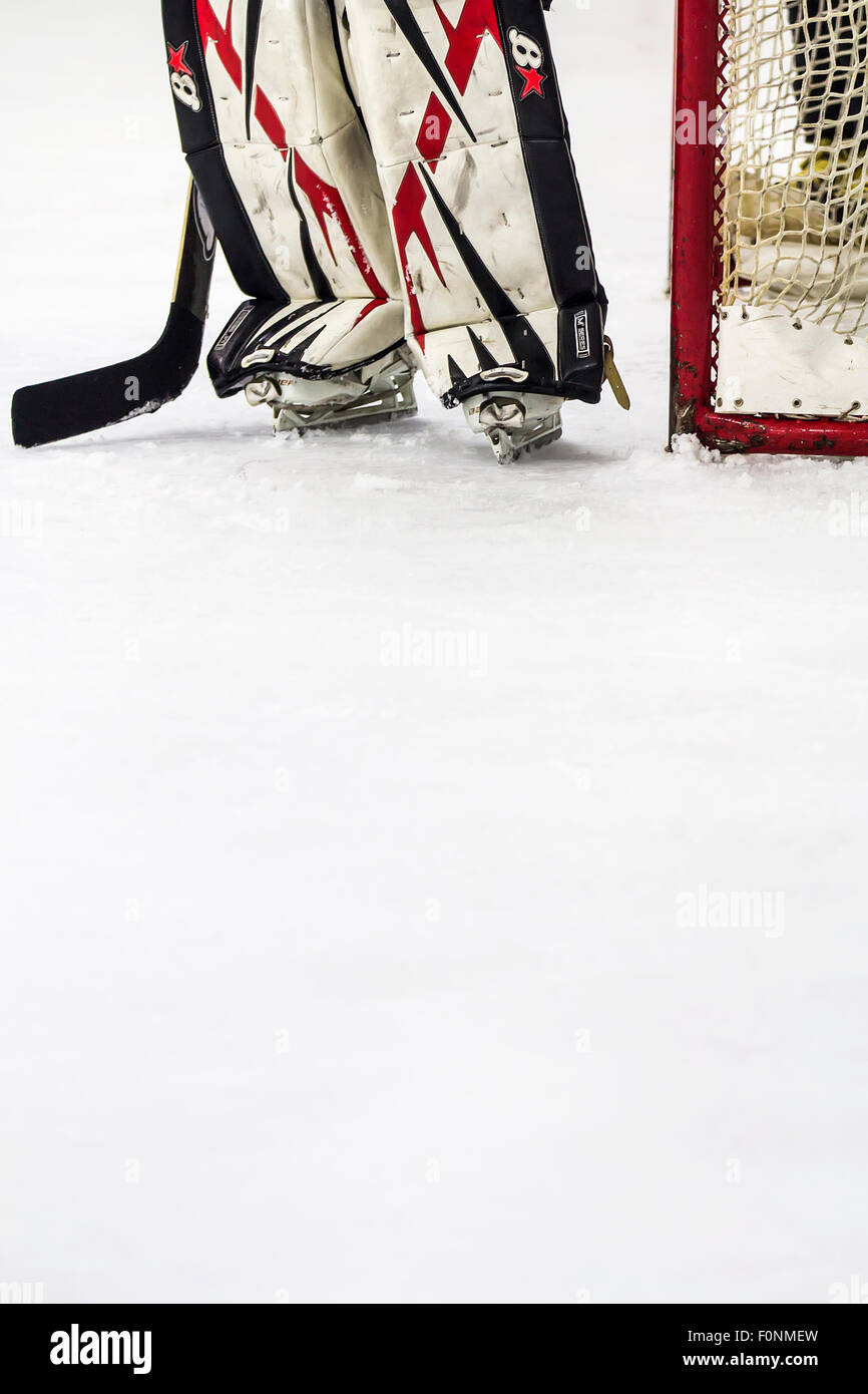 Ice hockey goalkeeper standing next to the goal on ice. - Stock Image