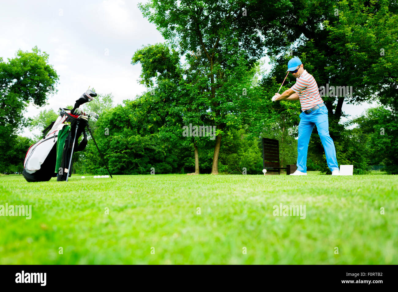 Golfer getting ready to hit the first long shot - Stock Image