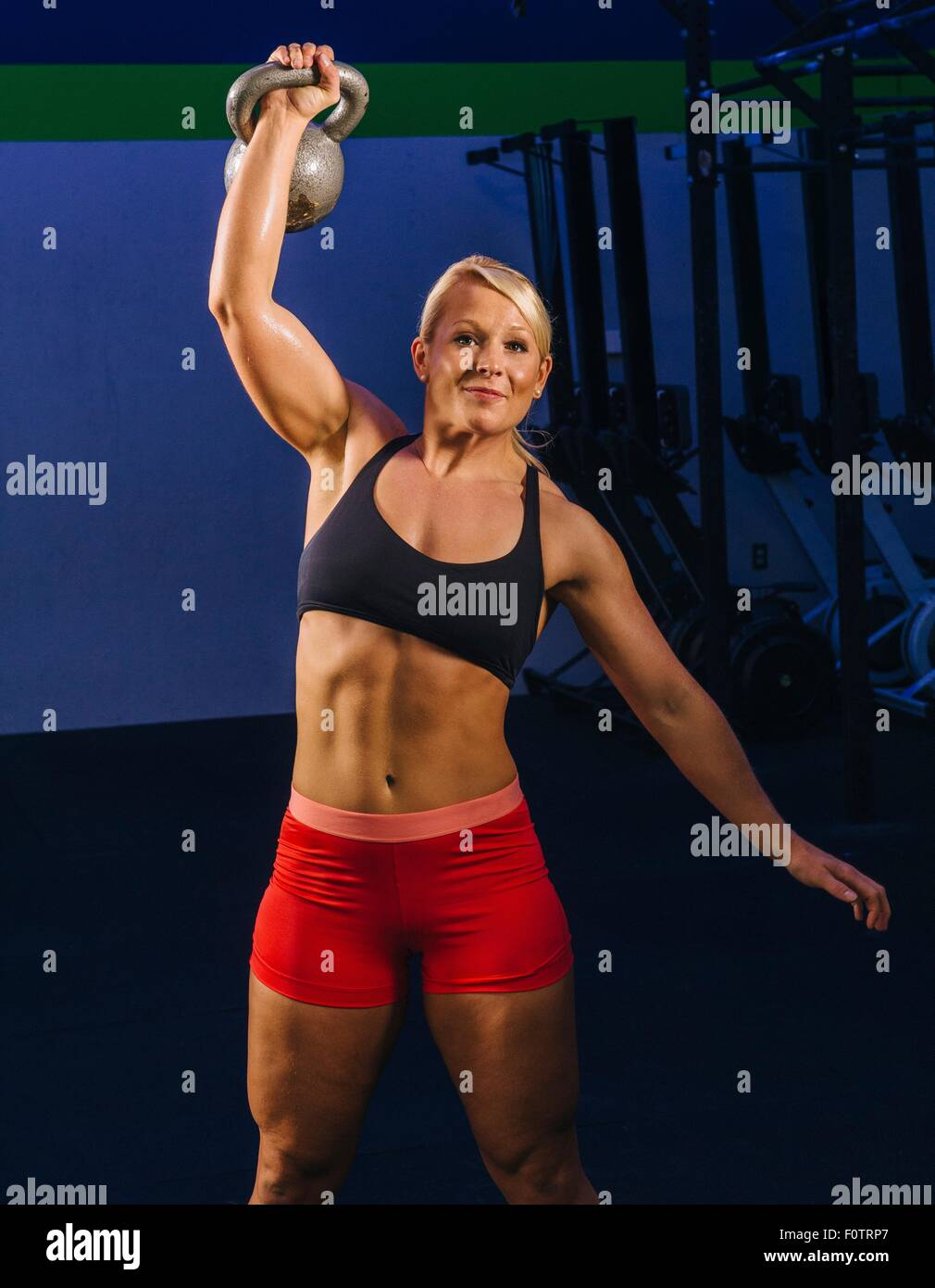 Young woman weightlifting kettlebell in gym - Stock Image