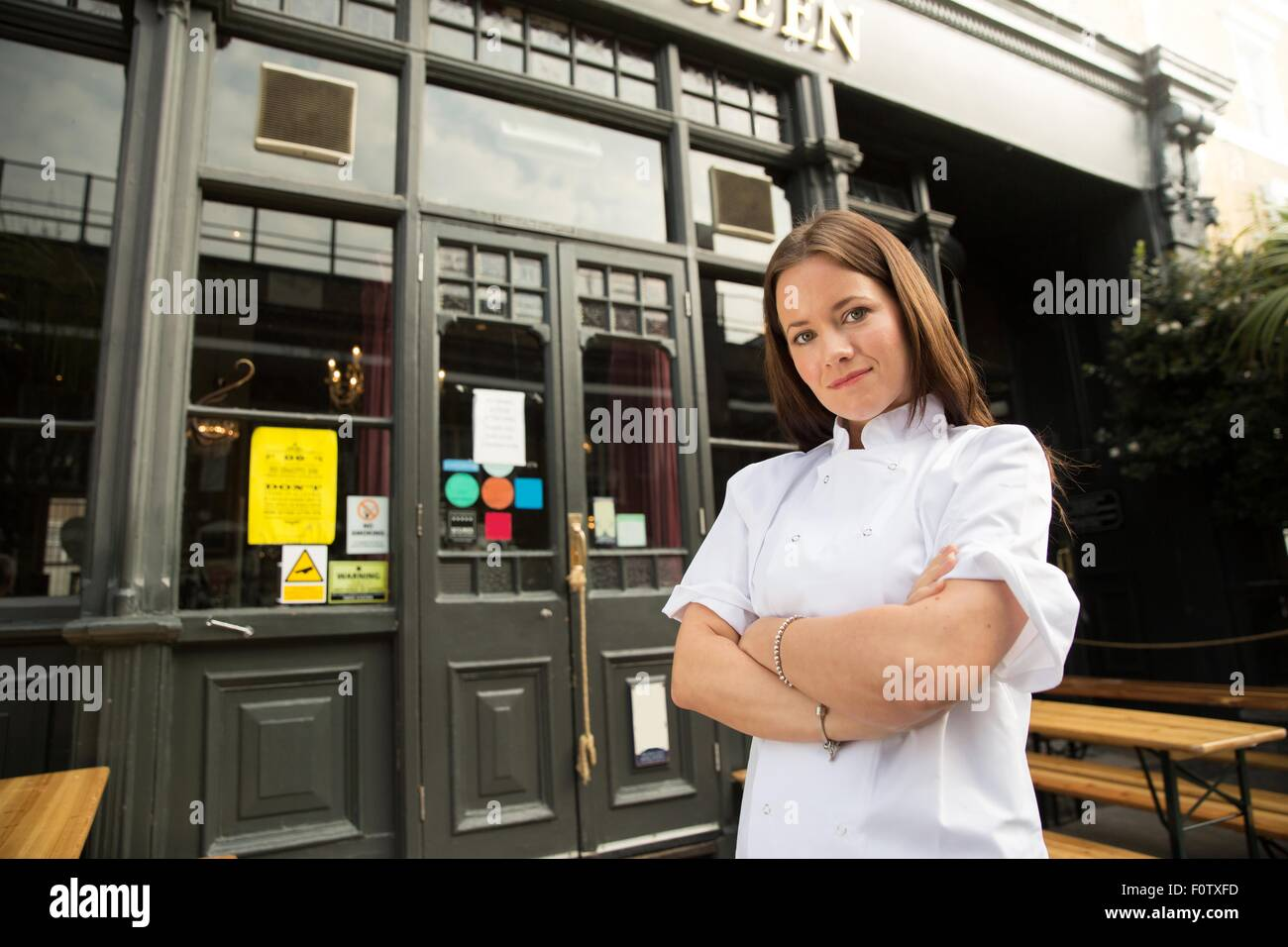 Mid adult chef standing outside of work arms folded - Stock Image
