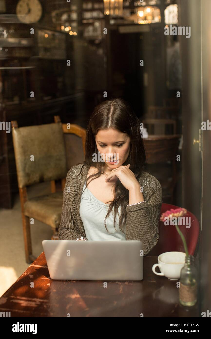 Mid adult woman sitting at table using laptop, hand on chin - Stock Image