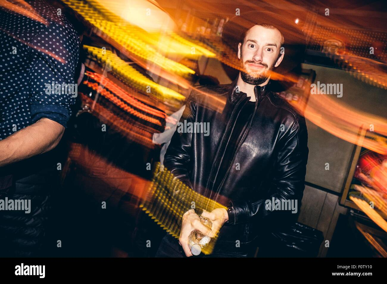Portrait of young man in bar, blurred motion - Stock Image