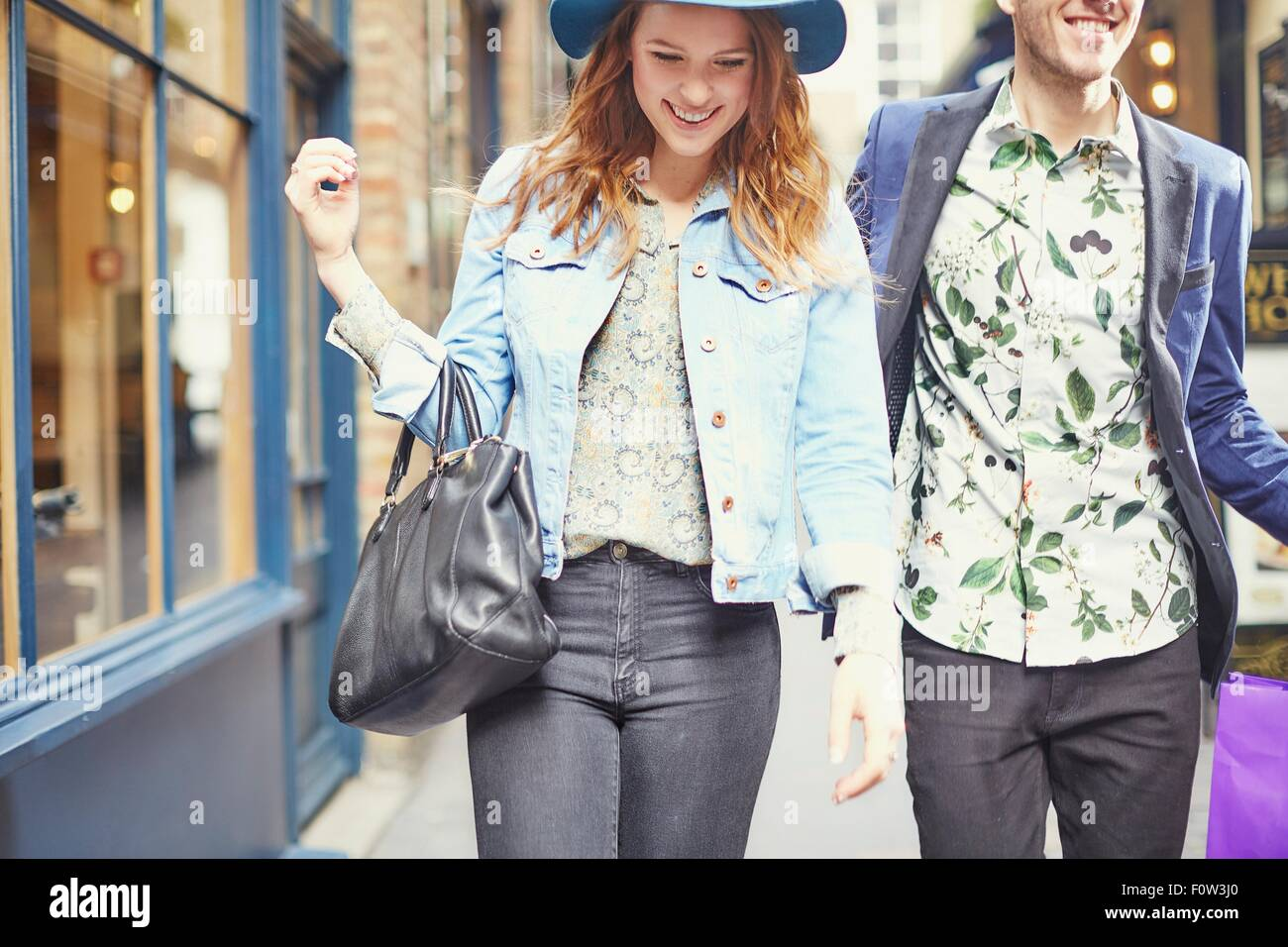 Cropped view of stylish couple out shopping, London, UK - Stock Image