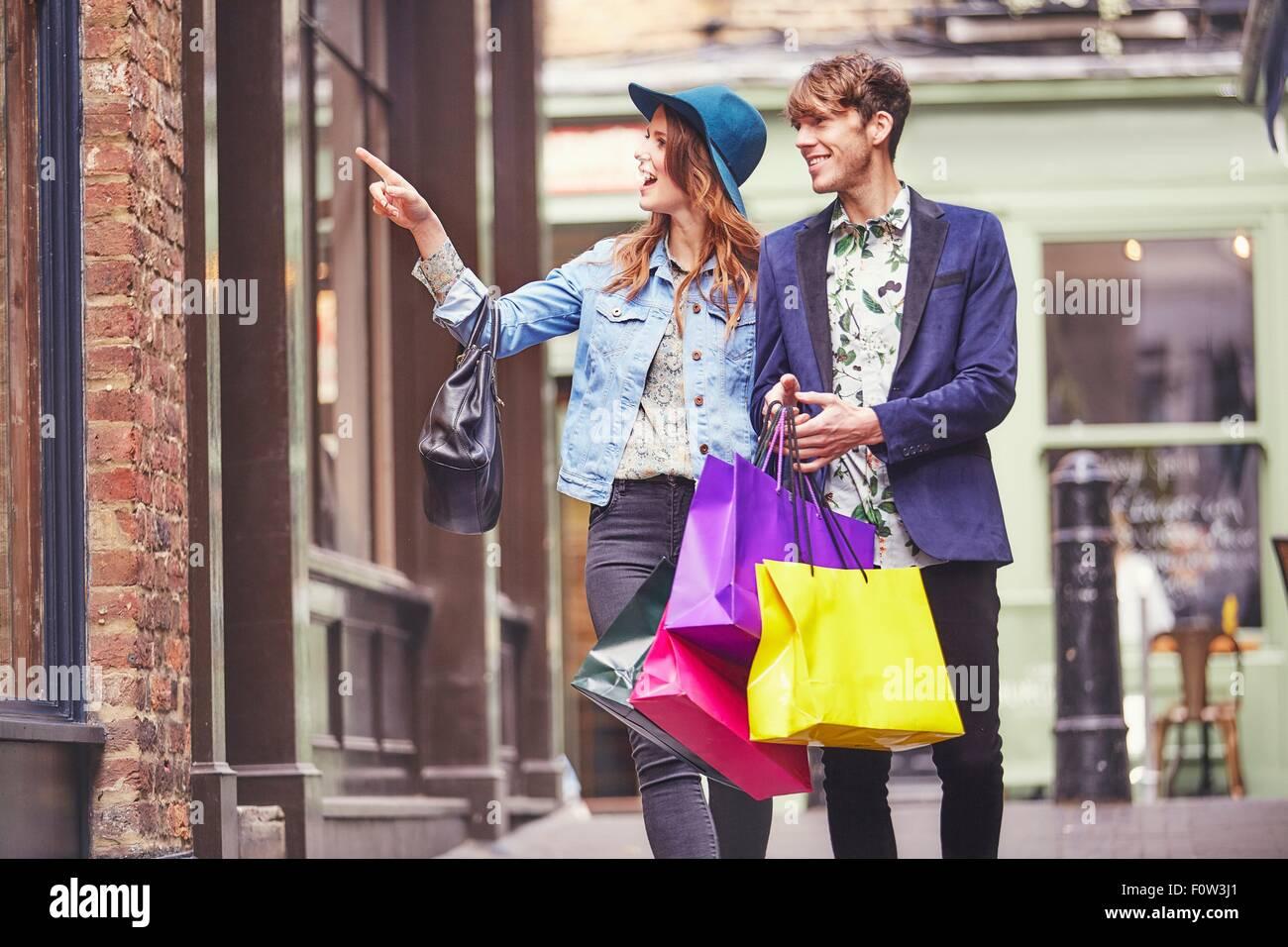 Stylish couple pointing at shop window, London, UK - Stock Image