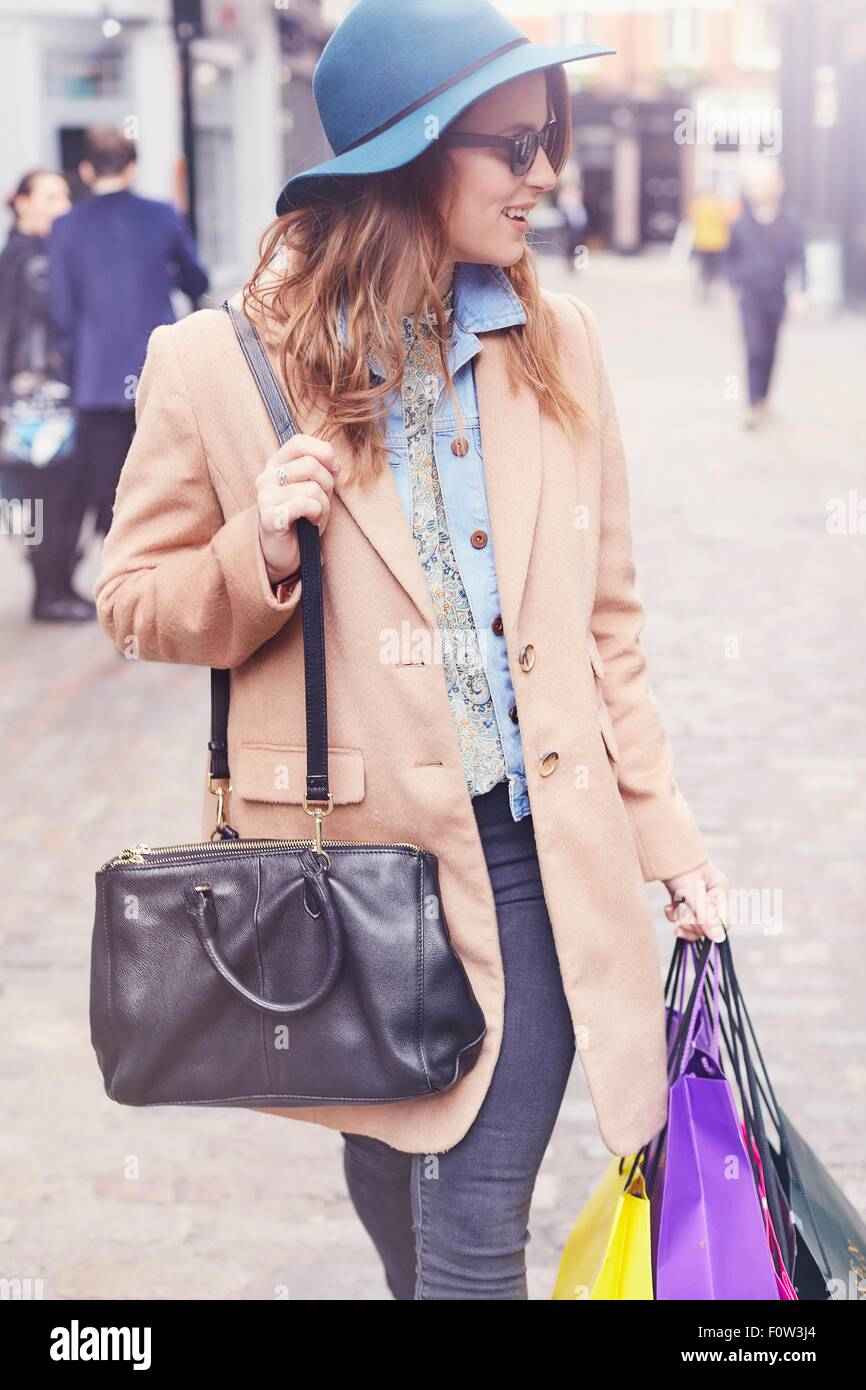 Stylish young female shopper looking over her shoulder, London, UK - Stock Image