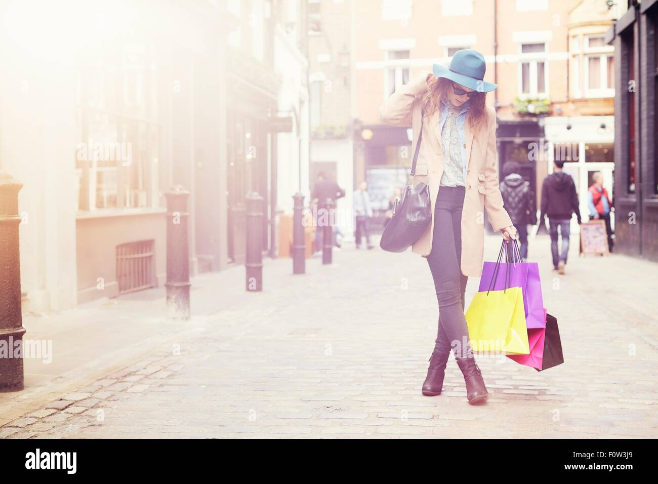 Portrait of stylish young woman with shopping bags, London, UK - Stock Image